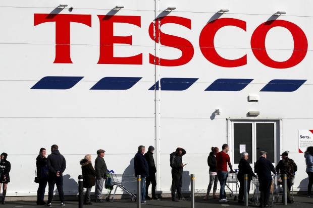 Leigh Journal: People queue outside a Tesco Extra store in Madeley, Shropshire