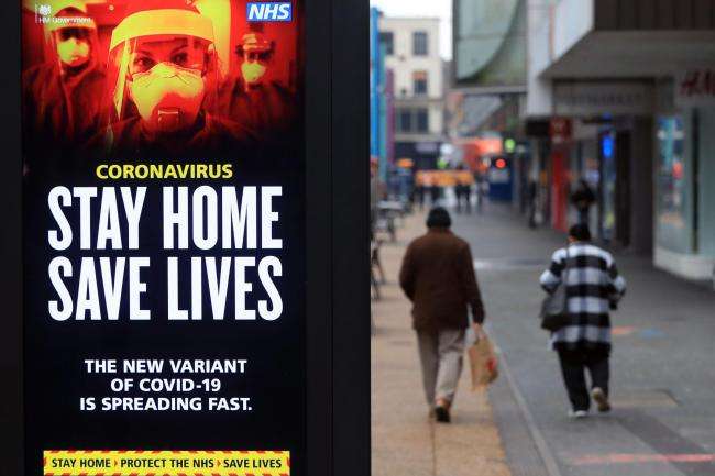 People pass a Stay Home, Save Lives electronic board in Leicester