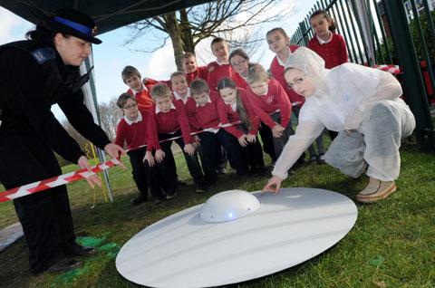 Intrigued pupils watch as PCSO Kirsty Jones and Falke Forensic Science Unit member Catherine Thompson check out the UFO