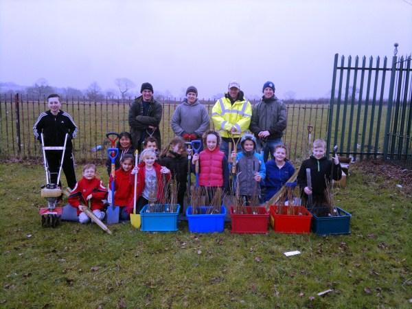 Pupils and volunteers prepare to plant a hedgerow at the Tyldesley school.