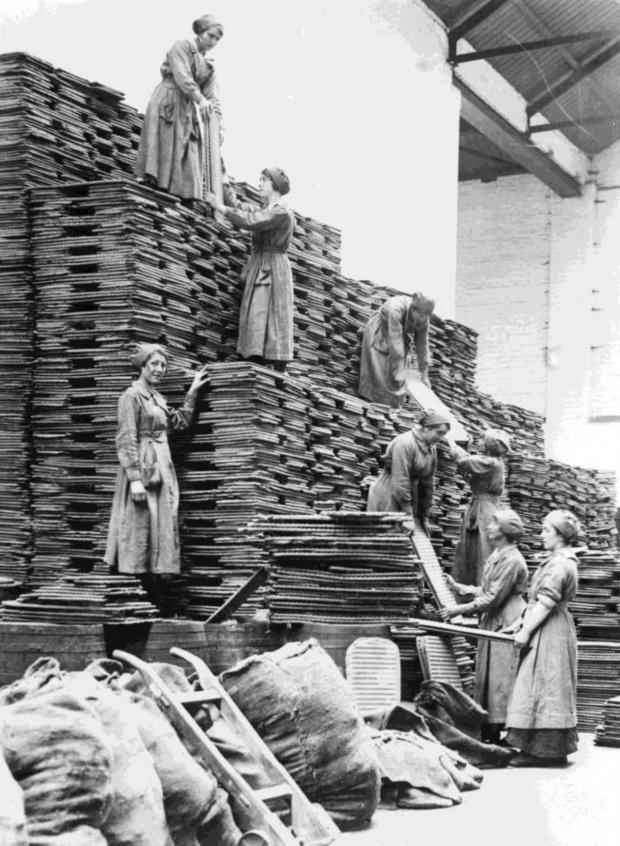 Leigh Journal: One of the pictures shows women workers stacking oil cakes at an oil and cake factory
