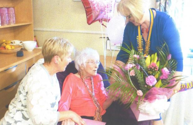 Janet receives birthday flowers from her daughter Catheryn, left, and Inner Wheel president Dorothy Bowker.