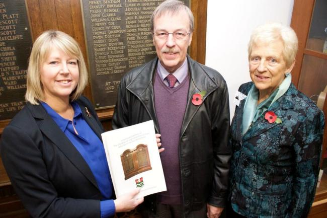 Head teacher Helen Phillips presents John Medling and Janet Evans with copies of the book