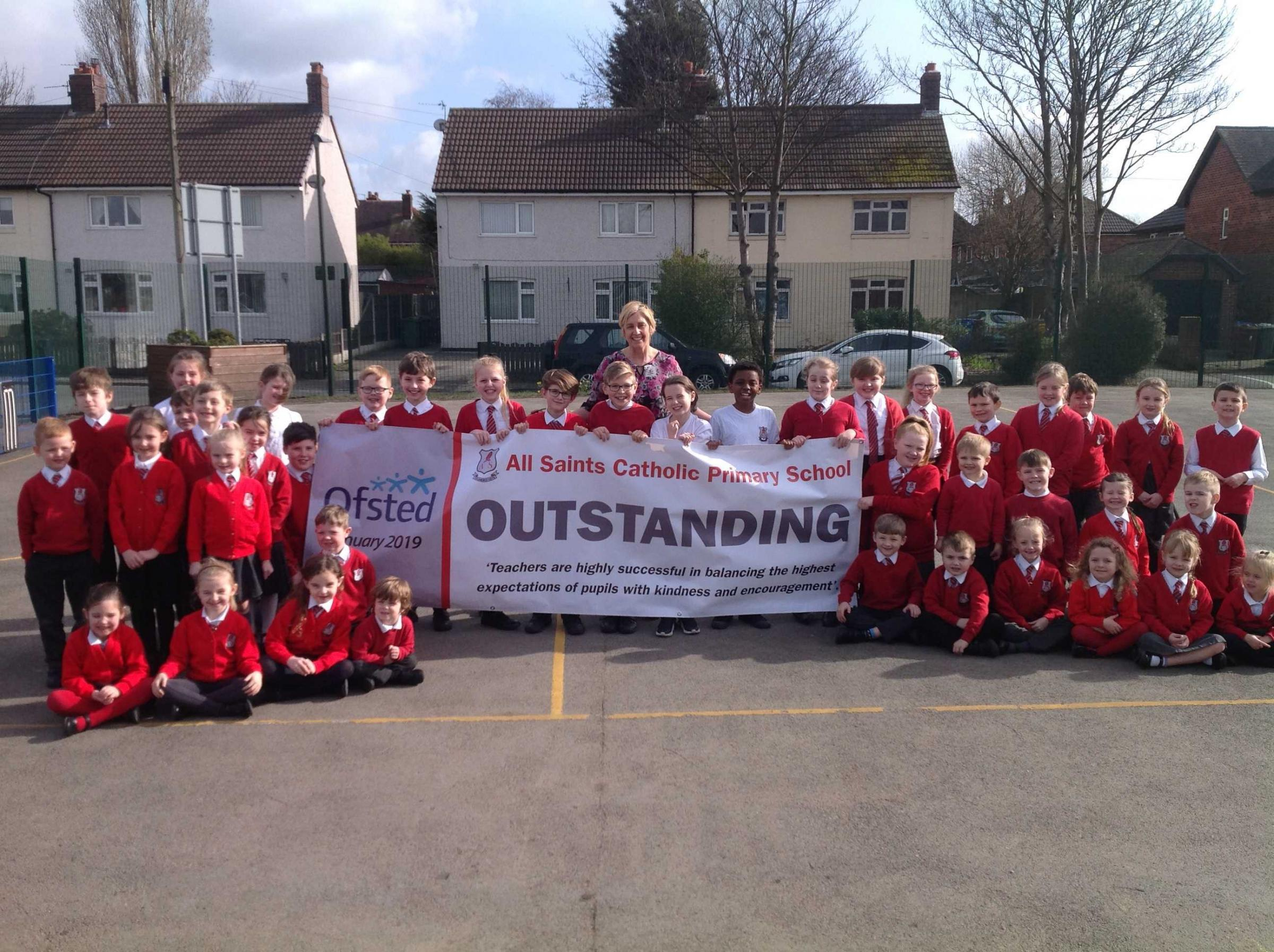 All Saints Catholic Primary School's pupils with head teacher Wendy Hughes, centre