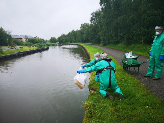 Teams work at the canal site on Plank Lane in Leigh on Thursday where the pollution incident was reported